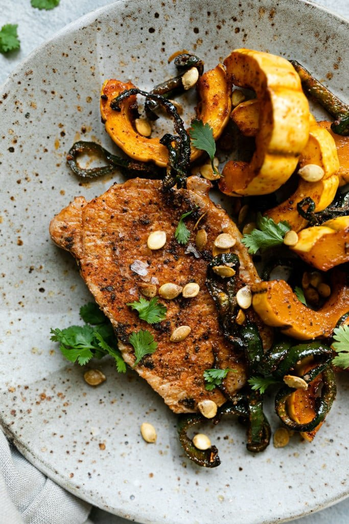 An oven baked pork chop seasoned with a side of delicata squash and poblano peppers plated on a speckled plate.