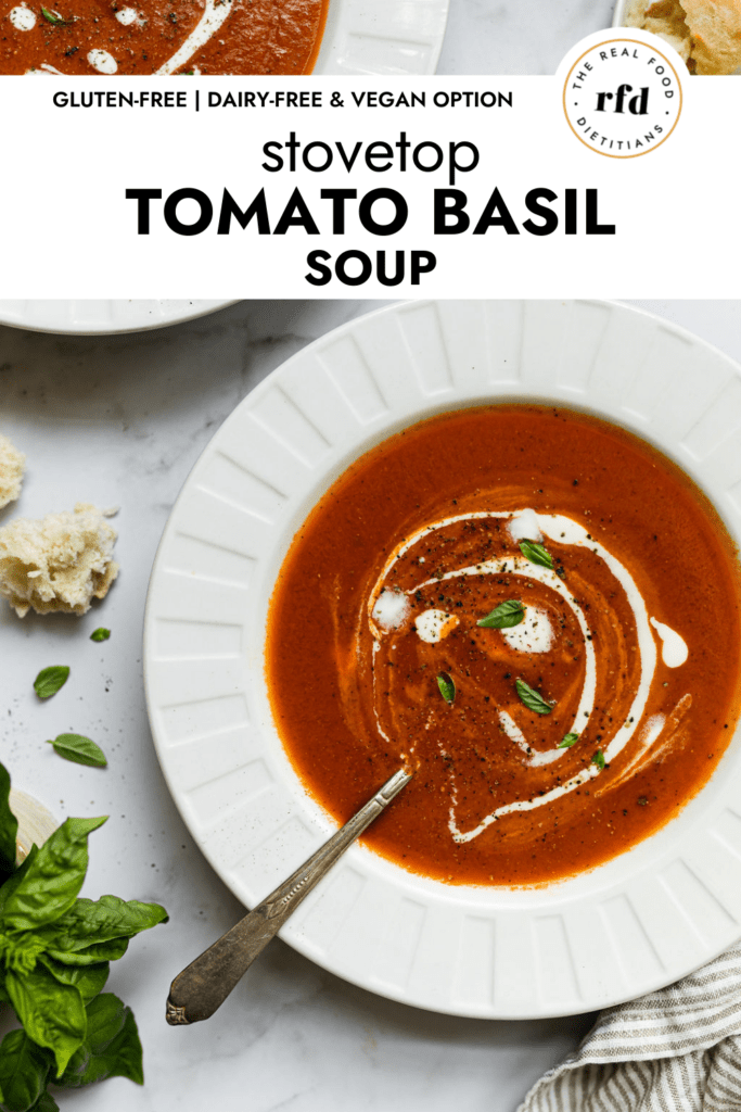 Creamy tomato basil soup in two white bowls with a swirl of cream, cracked black pepper, and fresh basil on top of each bowl.