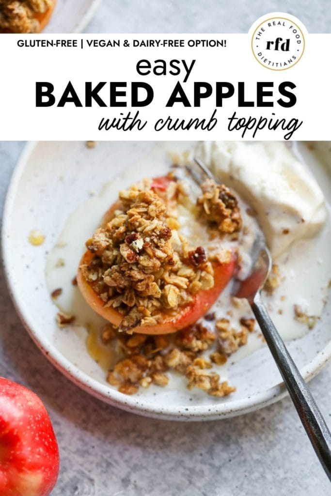 A baked apple half topped with oat and pecan crumble with a scoop of melting ice cream on a plate with a fork cutting into the soft apple.