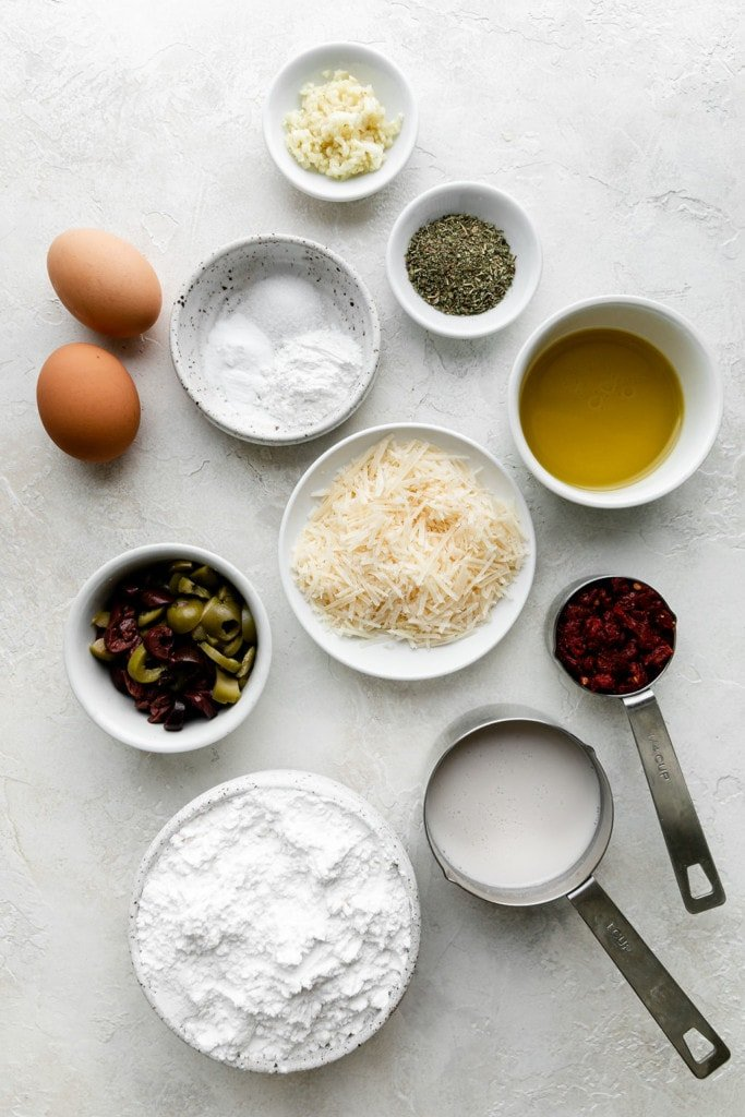 All ingredients for gluten-free olive bread in small bowls and measuring cups arranged together.