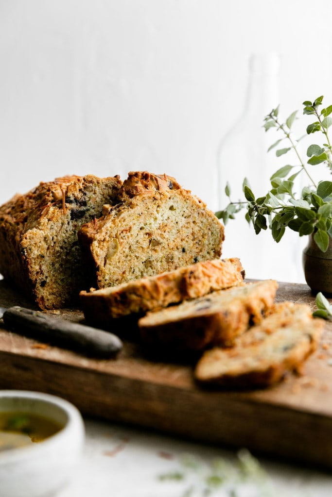A beautifully golden brown baked gluten-free olive bread loaf with thick slices cut from the loaf on a cutting board